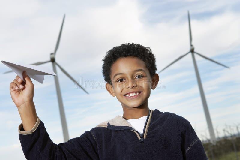 Jongen het Spelen met Document Vliegtuig bij Windlandbouwbedrijf royalty-vrije stock afbeelding