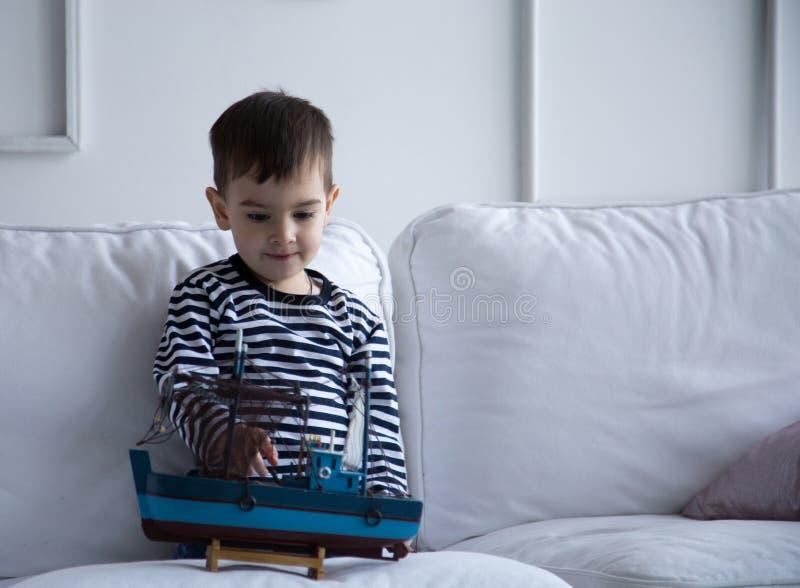 Jongen het spelen met een boot stock fotografie