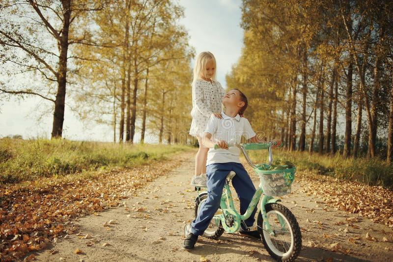 Jongen het spelen met een meisje in de herfstlandweg stock afbeelding