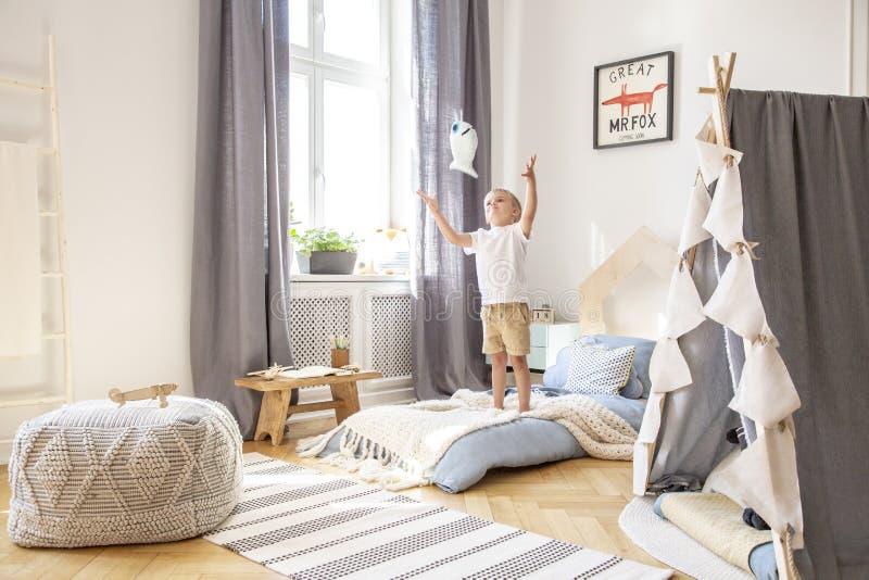 Jongen het spelen met een stuk speelgoed in een comfortabel binnenland van de kindspeelkamer royalty-vrije stock foto