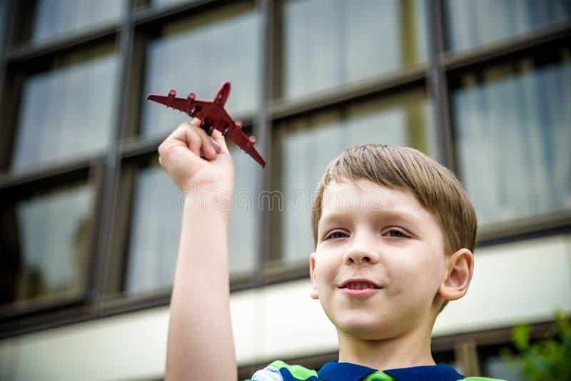 Jongen het spelen met een stuk speelgoed vliegtuig in het park op een de zomerdag Jongen die met een stuk speelgoed vliegtuig in  royalty-vrije stock foto