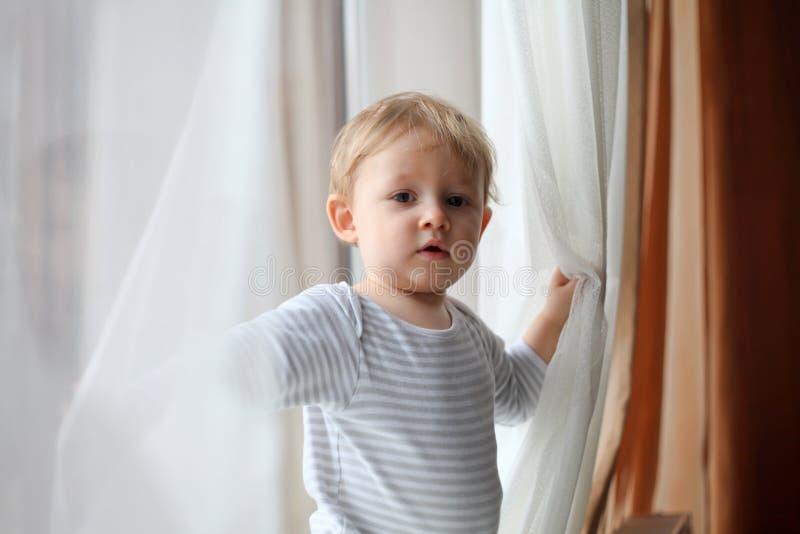 Jongen het spelen met gordijnen stock afbeelding