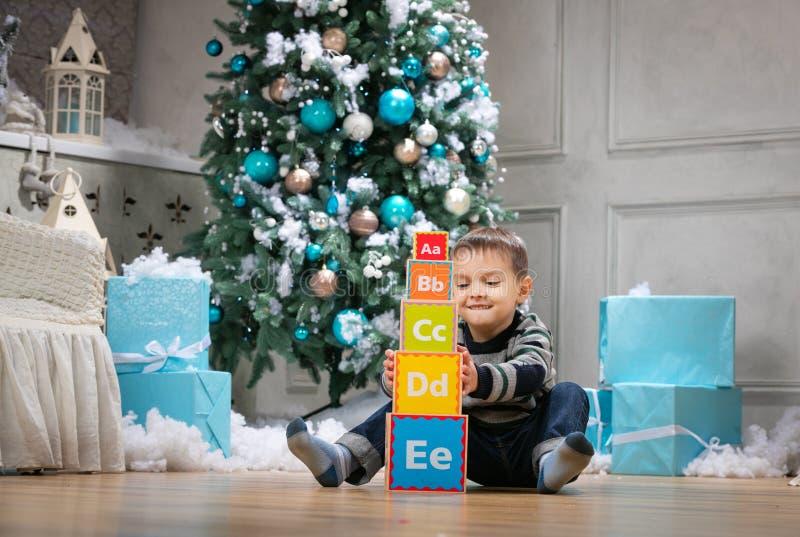 Jongen het spelen met houten alfabetblokken tegen Kerstboom royalty-vrije stock foto