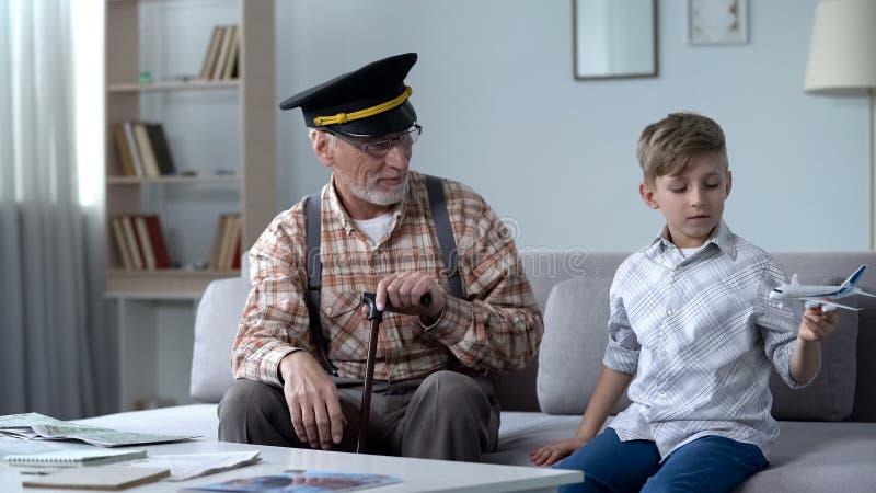 Jongen het spelen met stuk speelgoed vliegtuig, opa vroegere proef trots van kleinzoon, droombaan stock foto