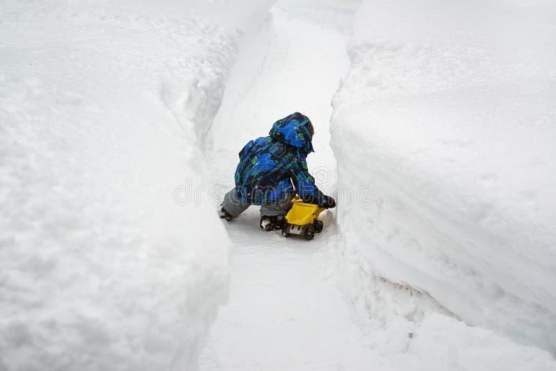 Jongen het Spelen met Toy Truck in Diepe Sneeuw stock foto's
