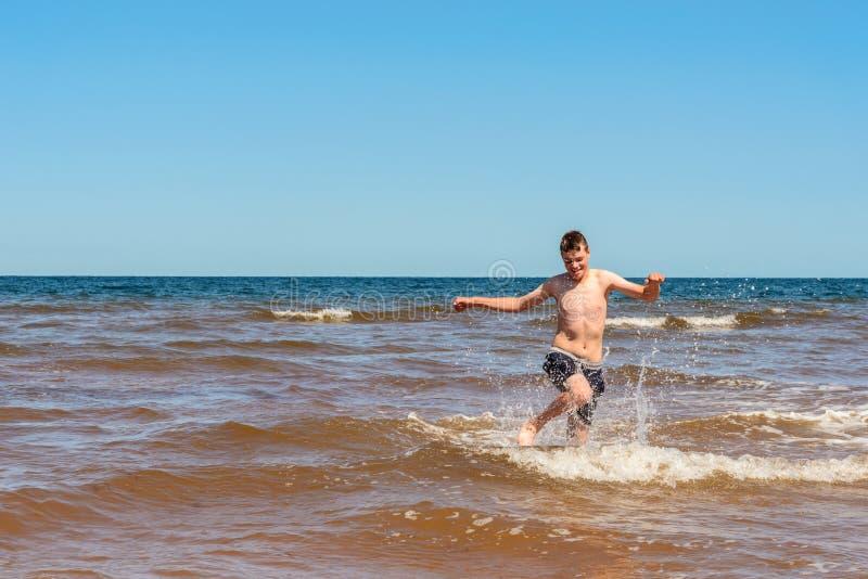 Jongen het spelen op het Cavendish-strand stock afbeeldingen