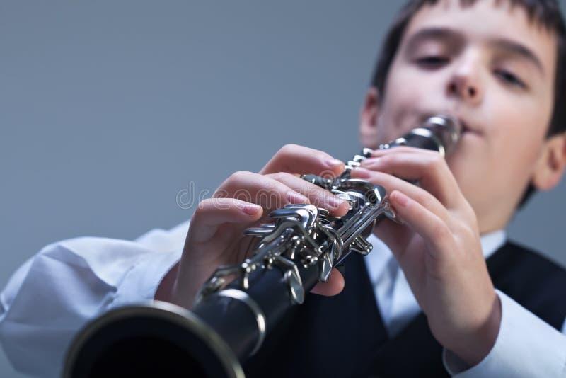Jongen het spelen op de klarinet stock foto's