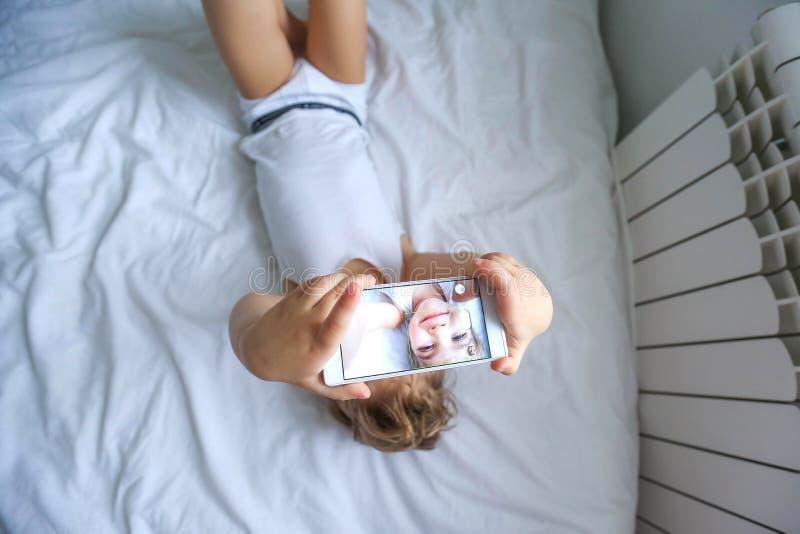 Jongen het spelen op elektronische gadgettablet in zijn slaapkamer Sociaal probleem van mededeling van kinderen in de moderne wer royalty-vrije stock foto
