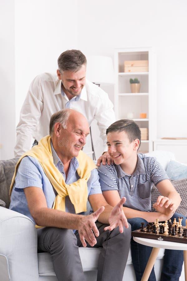 Jongen het spelen schaak met opa stock foto