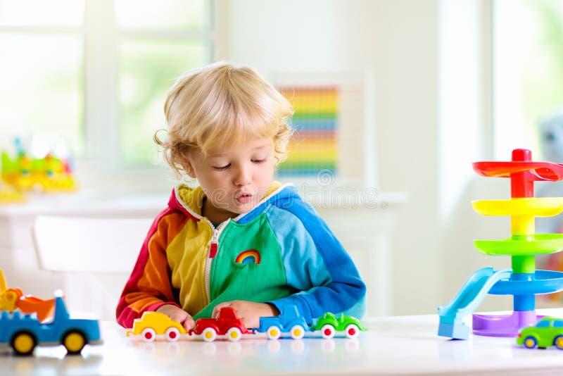 Jongen het spelen stuk speelgoed auto's Jong geitje met speelgoed kind en auto stock afbeeldingen