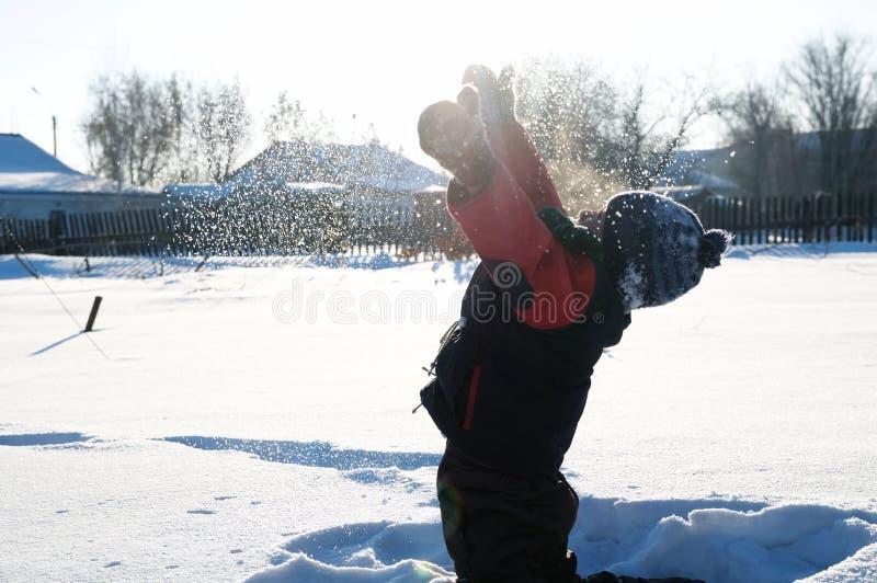 Jongen het spelen verspreidende sneeuw in de lucht, openluchtkinderenactiviteit in de winterkoude stock fotografie
