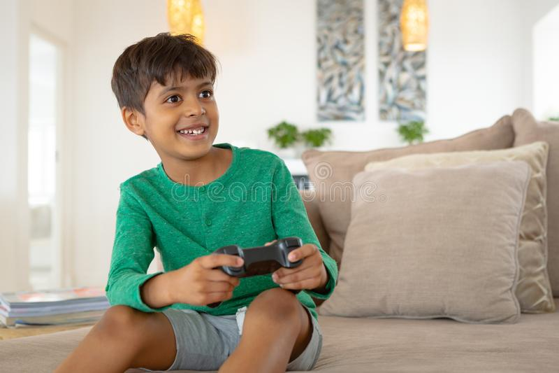 Jongen het spelen videospelletje op bank in woonkamer bij comfortabel huis stock fotografie