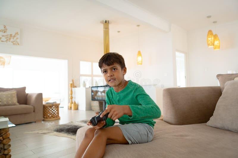 Jongen het spelen videospelletje op bank in woonkamer bij comfortabel huis stock foto's