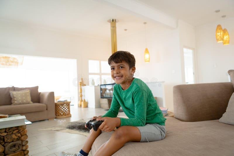 Jongen het spelen videospelletje op bank in woonkamer bij comfortabel huis royalty-vrije stock afbeeldingen