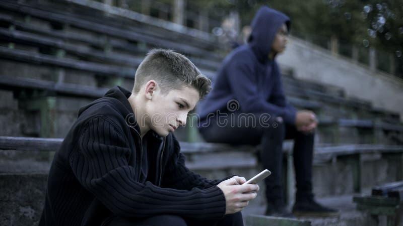 Jongen het spelen videospelletje op smartphone, aan sociaal netwerk wordt gewijd, digitale natie die stock afbeeldingen
