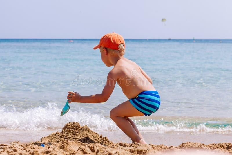 Jongen het spelen in het zand en golven op het strand royalty-vrije stock afbeeldingen