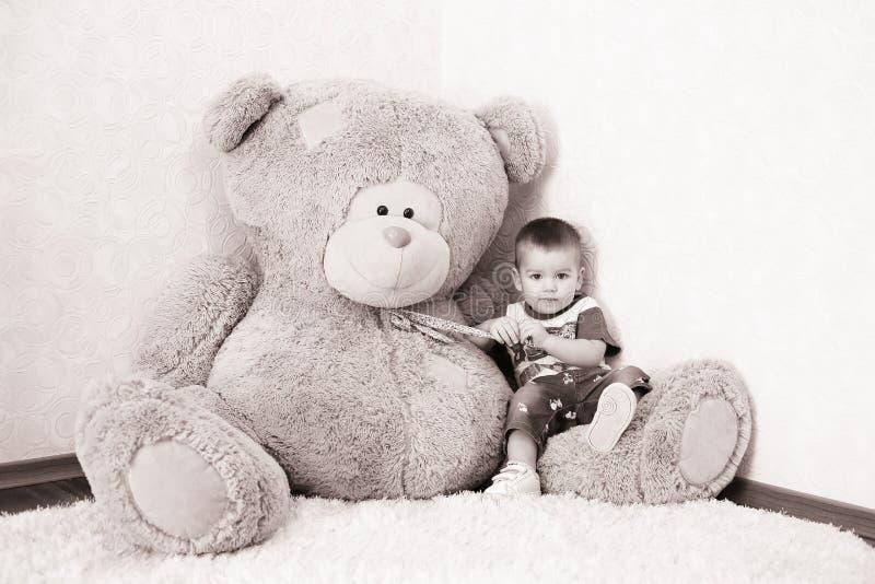 Jongen het stellen dichtbij een groot Teddybeer stock foto