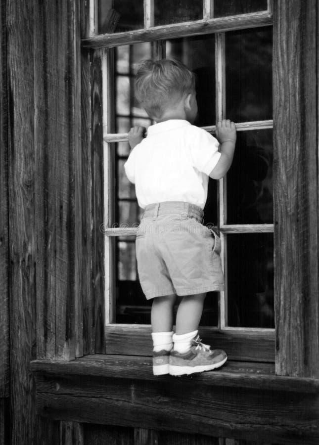 Jongen in het venster stock afbeeldingen
