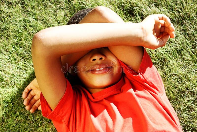 Jongen het verbergen van de zon stock foto