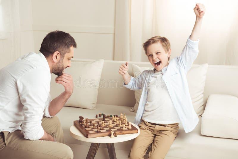 Jongen het vieren succes in schaakspel met dichtbij langs vader royalty-vrije stock fotografie