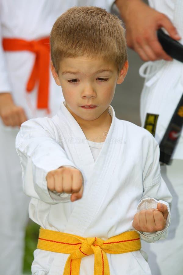 Jongen in karatekostuum opleiding stock fotografie
