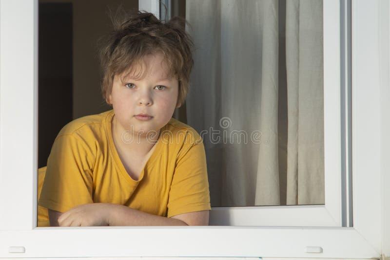 Jongen kijken in het raam in Pandemische isolatie - Kind in windowsill tijdens het coronovirus, covid-19 royalty-vrije stock fotografie
