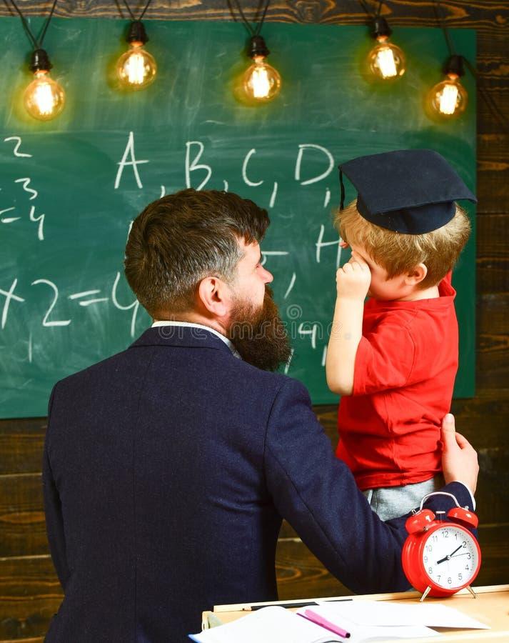 Jongen, kind die in gediplomeerd GLB gekrabbel op bord bespreken terwijl leraar het luisteren Leraar met baard, vader stock afbeelding