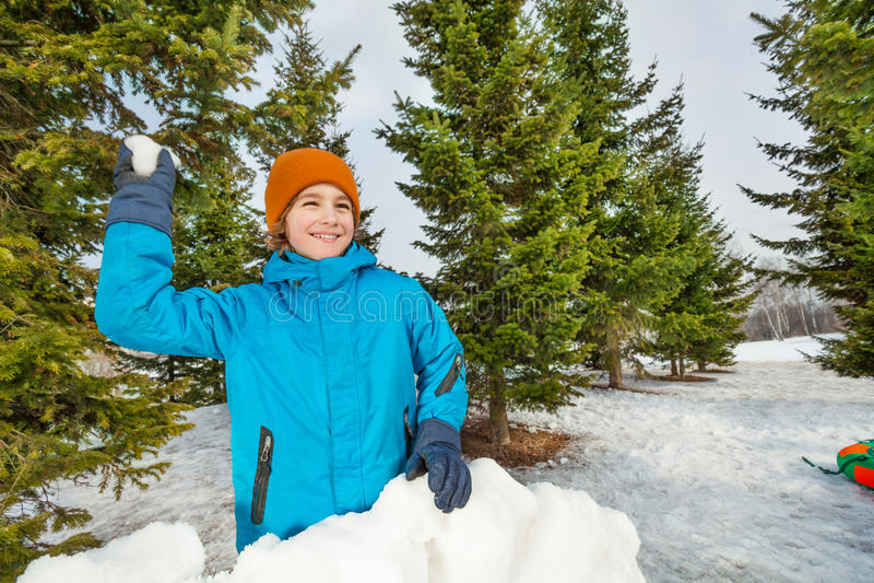 Jongen klaar om sneeuwbal tijdens spel te werpen royalty-vrije stock foto