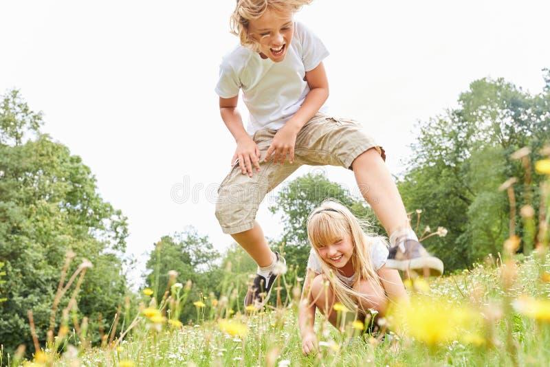 Jongen in leapfrog met zuster royalty-vrije stock foto's