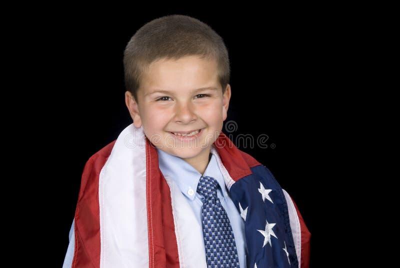 Jongen met Amerikaanse vlag rond schouders royalty-vrije stock afbeelding