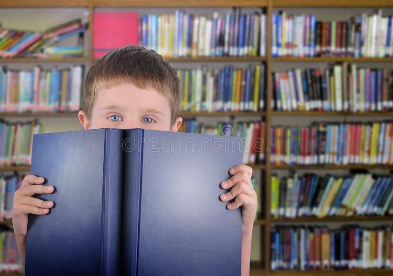 Jongen met Blauw Boek in Bibliotheek royalty-vrije stock fotografie