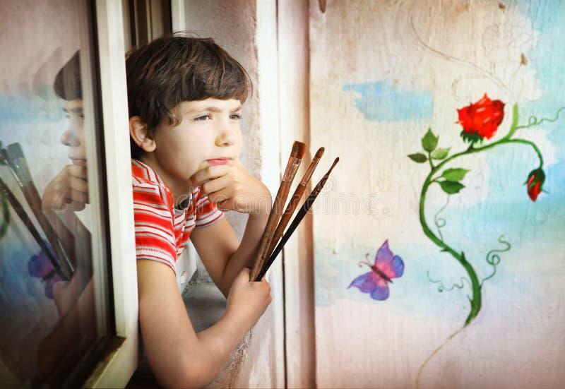 Jongen met borstels en zijn het schilderen stock foto's