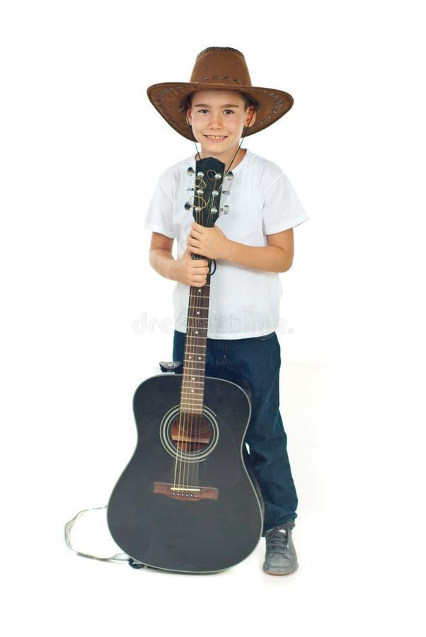 Jongen met cowboyhoed en gitaar stock foto