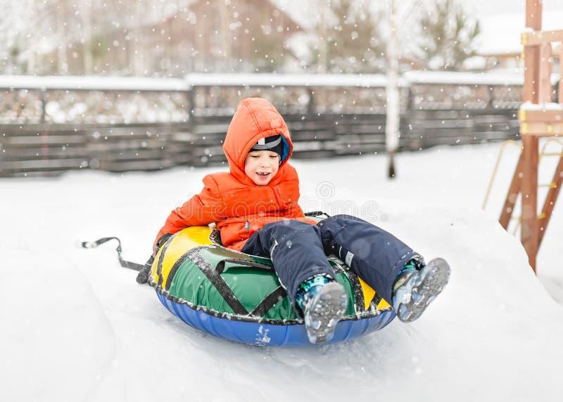 Jongen met de opblaasbare slee, sneeuwbuis stock fotografie