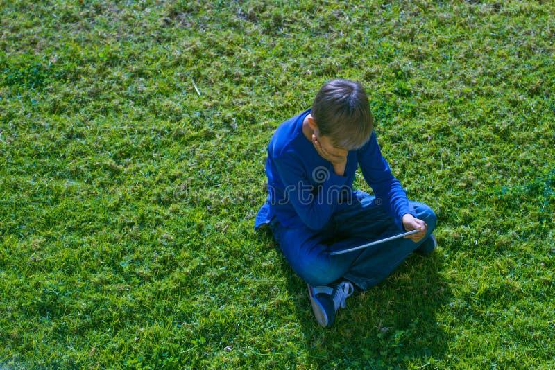 Jongen met de zitting van de tabletcomputer op het gras bij zonnige dag in openlucht royalty-vrije stock foto's