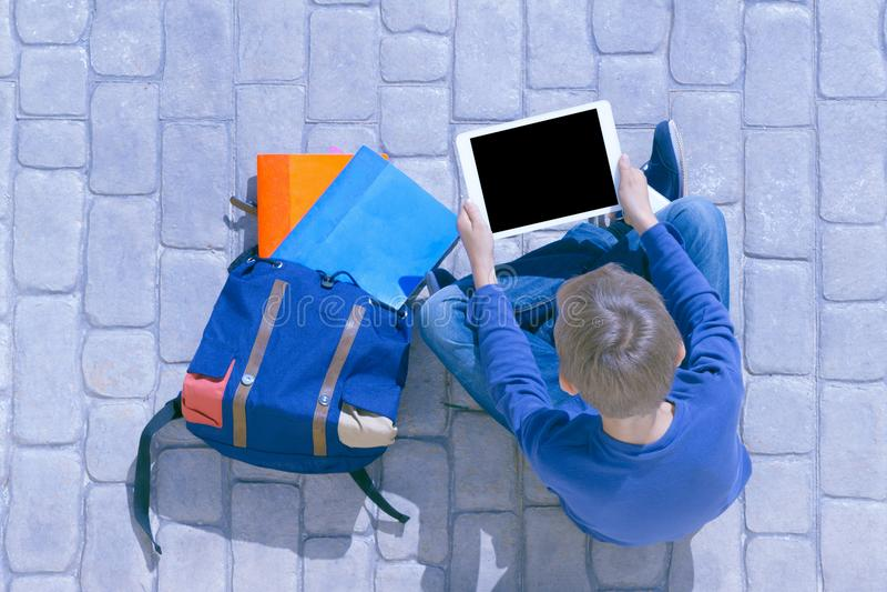 Jongen met de zitting van de tabletcomputer in openlucht dichtbij rugzak stock foto's