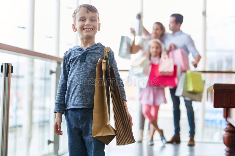 Jongen met document zakken terwijl het winkelen stock fotografie
