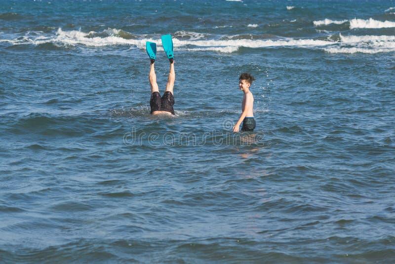 Jongen met duikende vader in de zwemmende vinnen boven de onweersgolven royalty-vrije stock afbeelding