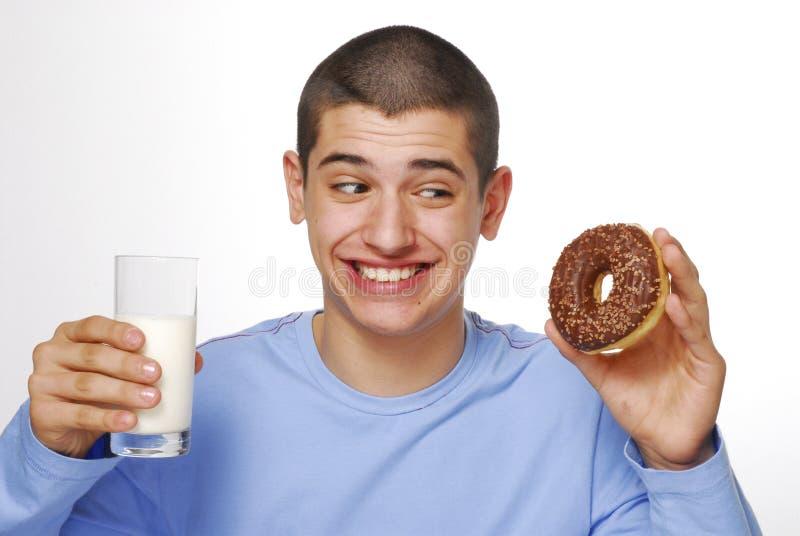 Jongen met een chocolade donuts. stock afbeeldingen