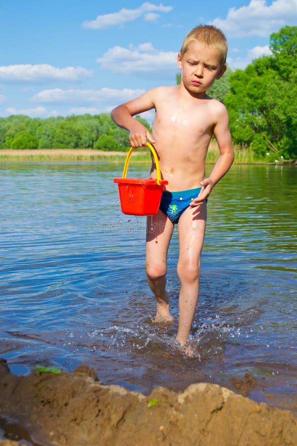 Jongen met een emmer water stock afbeelding