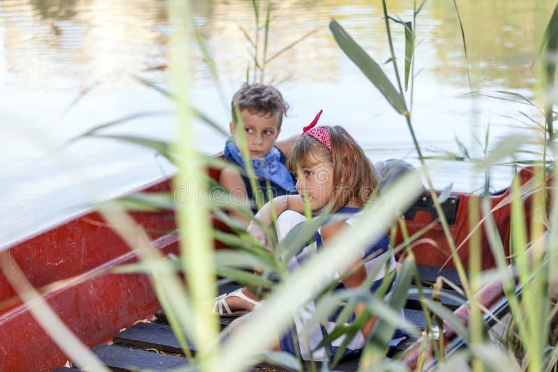 Jongen met een meisje die op een boot op het meer in de zomer zonnige dag berijden stock afbeeldingen