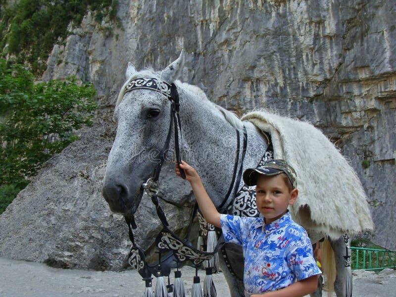 Jongen met een paard bij de rots stock afbeeldingen
