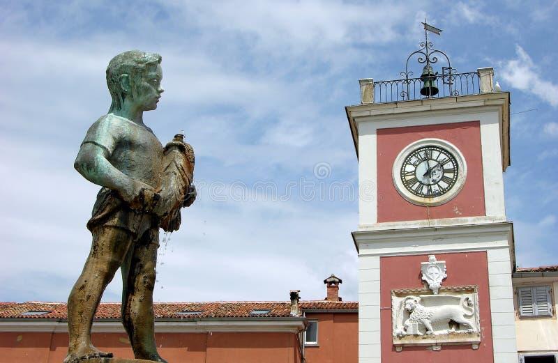 Jongen met een vissenstandbeeld in Rovinj, Kroatië royalty-vrije stock foto's