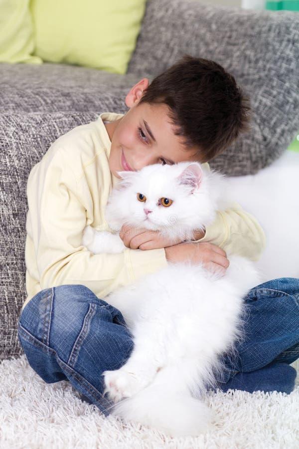 Jongen met een witte Perzische kat thuis royalty-vrije stock foto's