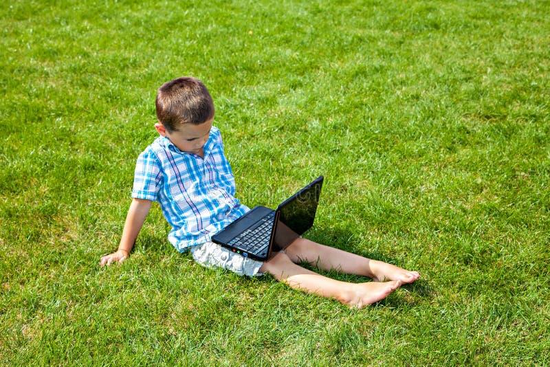 Download Jongen Met Laptop Zitting Op Het Gras Stock Afbeelding - Afbeelding bestaande uit toetsenbord, activiteit: 39106631