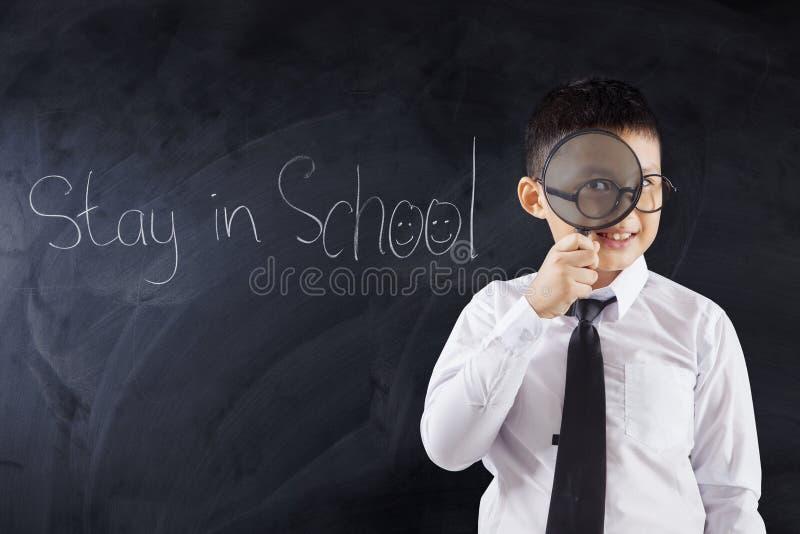 Jongen met meer magnifier en tekstverblijf in School stock afbeelding