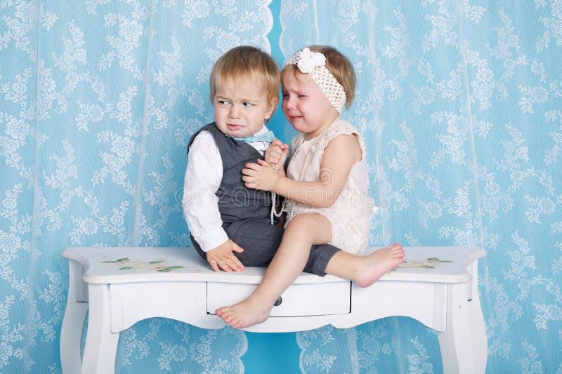 Jongen met meisje zitting en het schreeuwen stock foto's