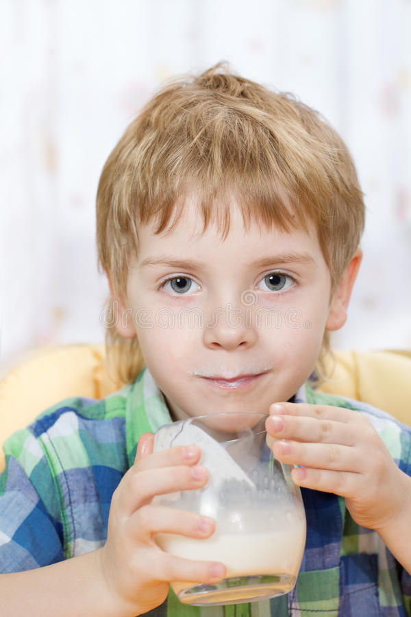 Jongen met melksnor na het drinken van glas royalty-vrije stock afbeeldingen