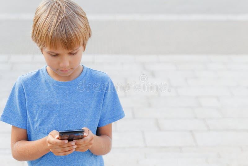 Jongen met mobiele telefoon in de straat Kind die het scherm, speelspelen bekijken, die apps gebruiken De achtergrond van de stad royalty-vrije stock afbeeldingen
