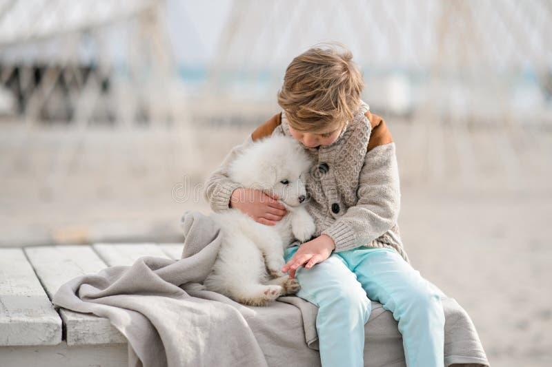 Jongen met puppyspel op het strand stock foto